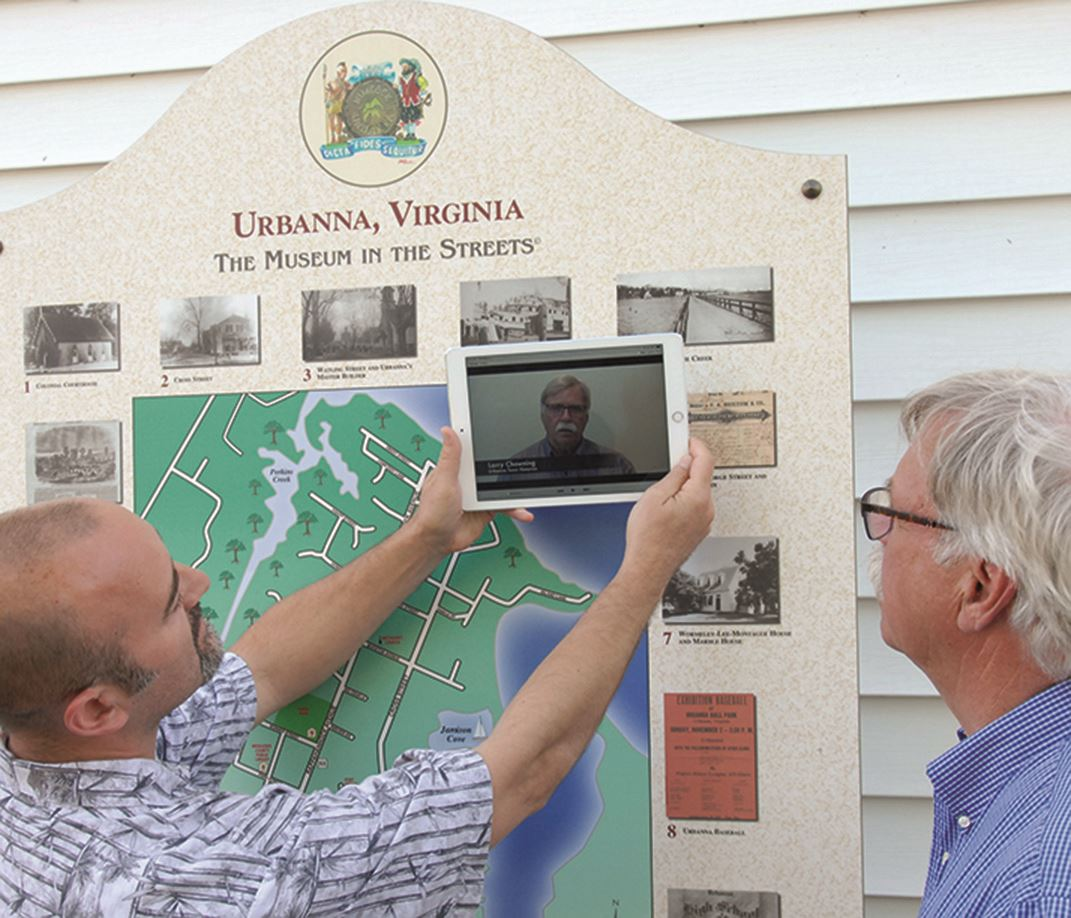 Individuals using an app on their tablet for a walking history tour of Ubranna
